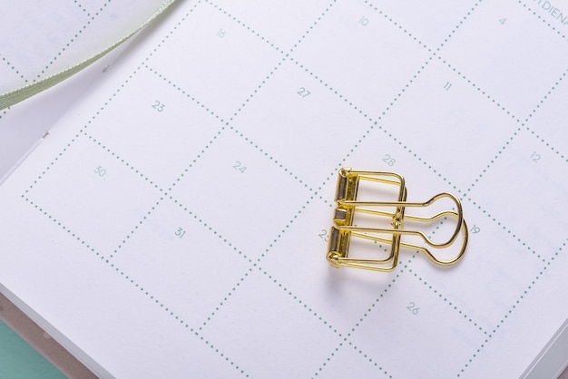 Goldene büroklammer auf kalenderorganisator-notizbuch