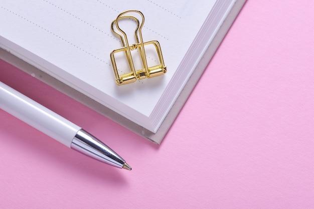 Goldene büroklammer und bleistift auf kalenderorganisator-notizbuch