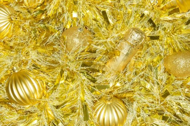 Goldene champagnerflasche mit lametta und weihnachtskugeln festlicher hintergrund