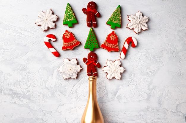 Goldene champagnerflasche mit weihnachts-lebkuchen-flatlay