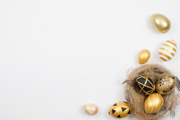 Goldene dekorierte ostereier im nest lokalisiert auf weißer oberfläche. minimales osterkonzept.
