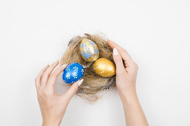 Goldene dekorierte ostereier im nest mit frauenhänden lokalisiert auf weißer oberfläche. minimales osterkonzept.