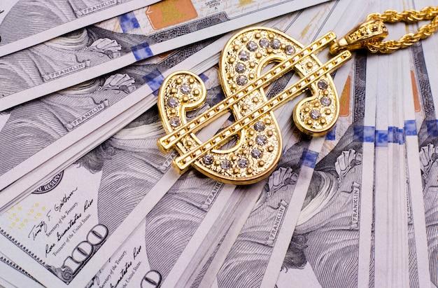 Goldene dollarzeichenhalskette auf us-dollars banknoten