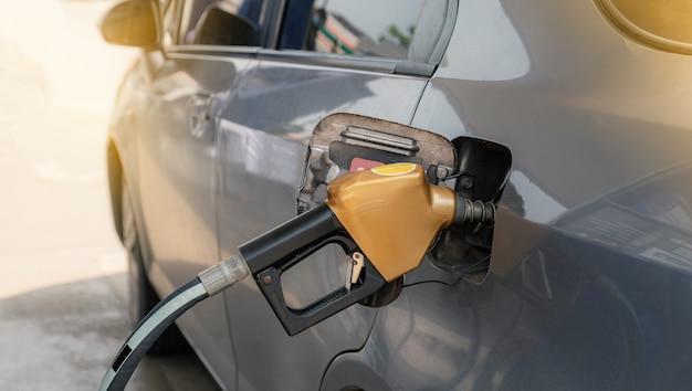 Goldene düsenpumpe pistolenbenzin von der ölpumpe im autotank zum tanken.