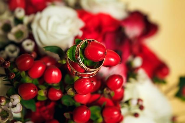 Goldene eheringe auf dem hintergrund eines hochzeitsblumenstraußes der roten rosen