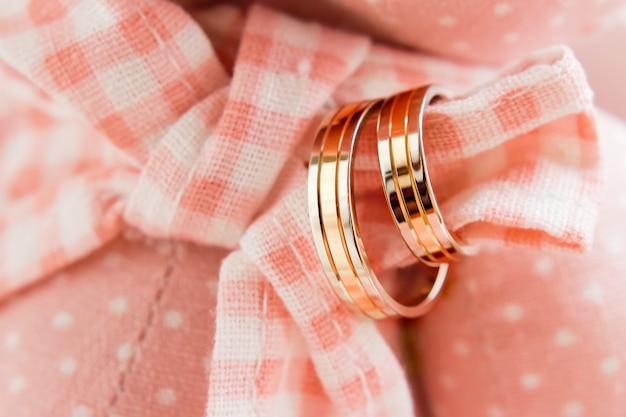 Goldene eheringe auf rosa plaidgewebe. hochzeitsschmuck details.
