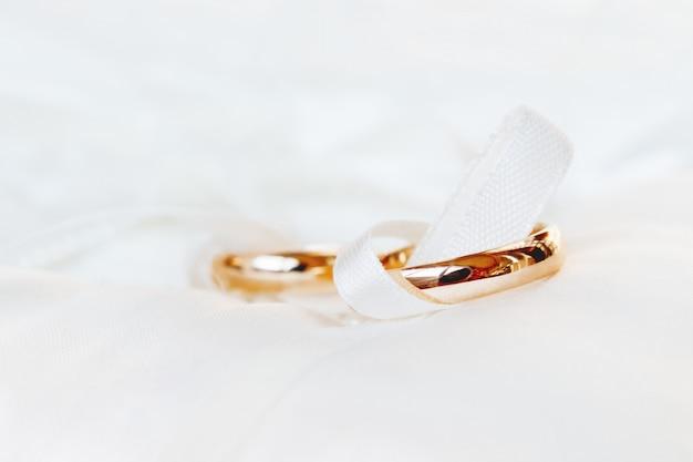 Goldene eheringe auf weißem silk hintergrund. hochzeitsdetails.