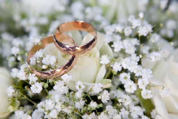 Goldene eheringe des bräutigams und der braut liegen auf einem strauß der braut