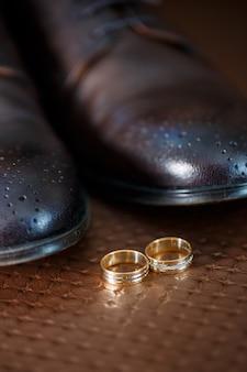 Goldene eheringe des brautpaares liegen neben herrenschuhen für den bräutigam
