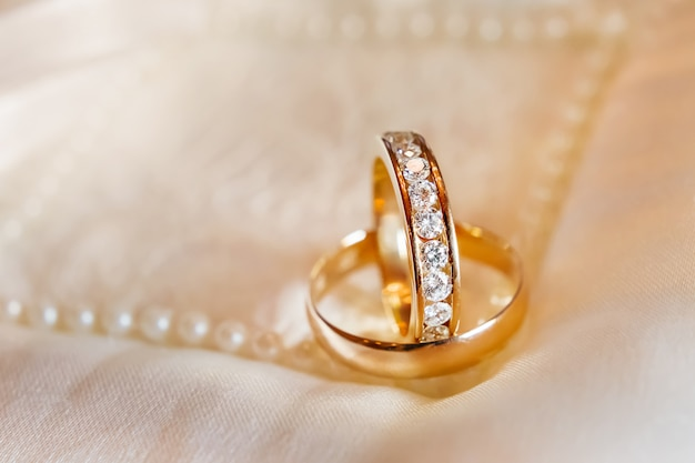 Goldene eheringe mit diamanten auf seidenstoff. hochzeitsschmuck details.