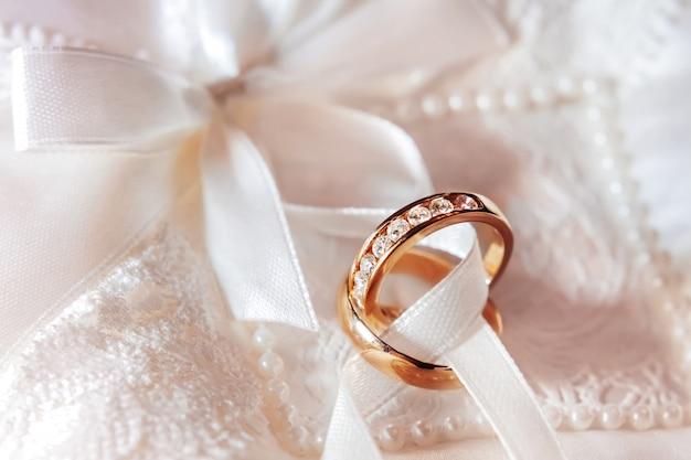 Goldene eheringe mit diamanten auf stoff. hochzeitsschmuck details. verlobungsring mit edelsteinen.