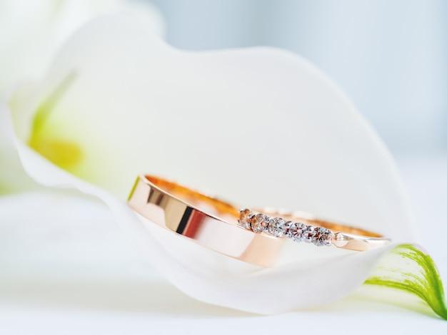 Goldene eheringe mit diamanten liegen innerhalb der callalilienblume. symbol der liebe und der heirat, traditionelles teures zubehör für braut und bräutigam.