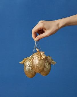 Goldene eicheln der weihnachtsdekoration in einer frauenhand