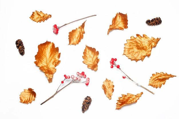 Goldene eichenblätter, rote beeren und tannenzapfen auf weißem hintergrund. herbststimmung.
