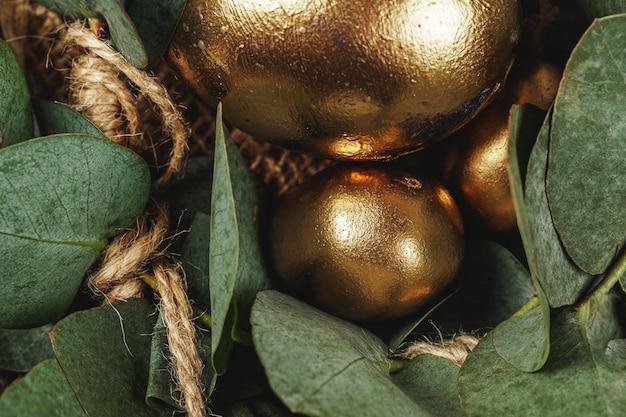 Goldene eier für osterkomposition mit blumigen zweigen