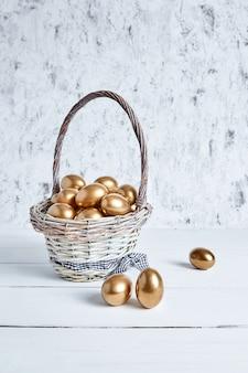 Goldene eier im korb auf weißem holztisch