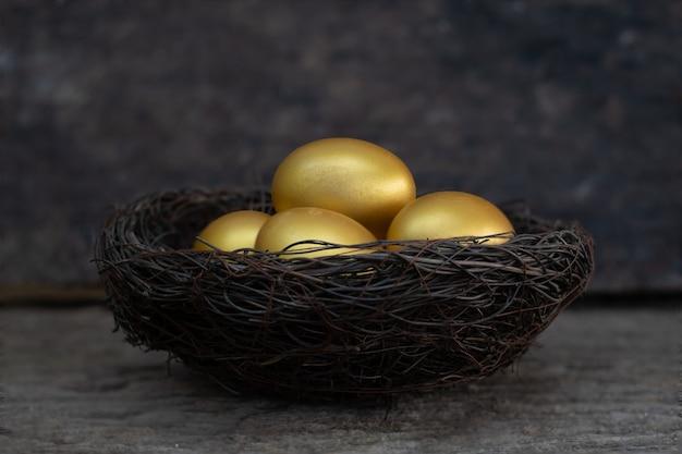 Goldene eier in einem nest auf dem alten holztisch