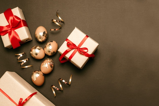 Goldene eier mit überraschungsgeschenkboxen auf einem dunklen hintergrund mit platz für text. rote schleife bögen dekoration. festliche osterkomposition