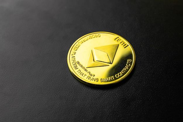 Goldene ethereum-kryptowährungsmünze nahaufnahme auf schwarzem hintergrund, symbolfoto