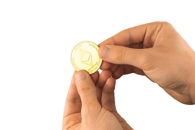 Goldene ethereum-münze in den händen isoliert auf weißem hintergrundfoto