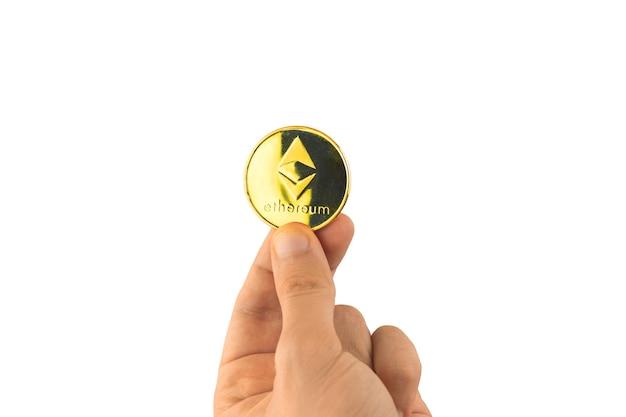 Goldene ethereum-münze in männlicher hand isoliert auf weißem hintergrund, kryptowährungsfoto
