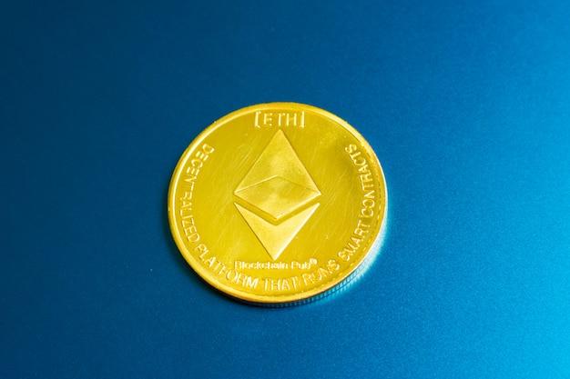 Goldene ethereummünze mit ethereumsymbol auf einer laptoptastatur nahe bei der eingabetaste