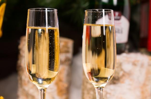 Goldene farbweine für partner auf eleganten flötengläsern in paralleler position hautnah.