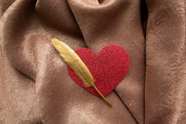 Goldene feder und glänzendes valentinstagherz auf braunem vorhangstoff