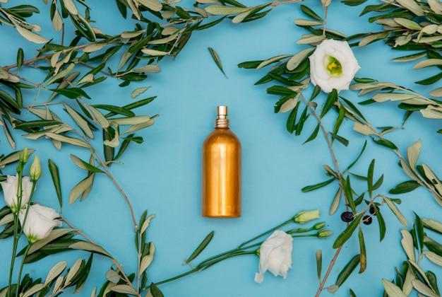 Goldene flasche mit olivenzweigen auf blauem hintergrund.