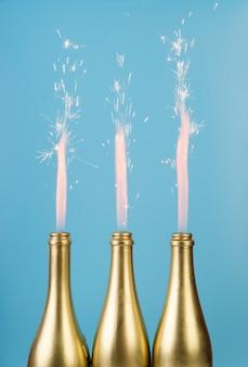 Goldene flaschen der vorderansicht mit feuerwerken