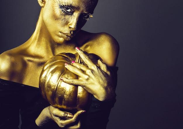 Goldene frau mit halloween-kürbis