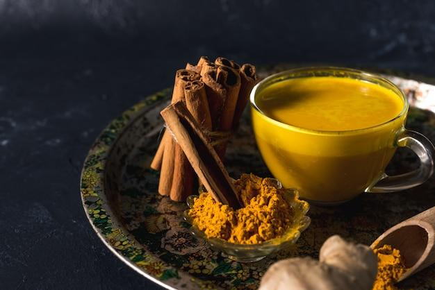 Goldene gelbwurzmilch auf der dunklen oberfläche mit gewürzzimt und -bestandteilen