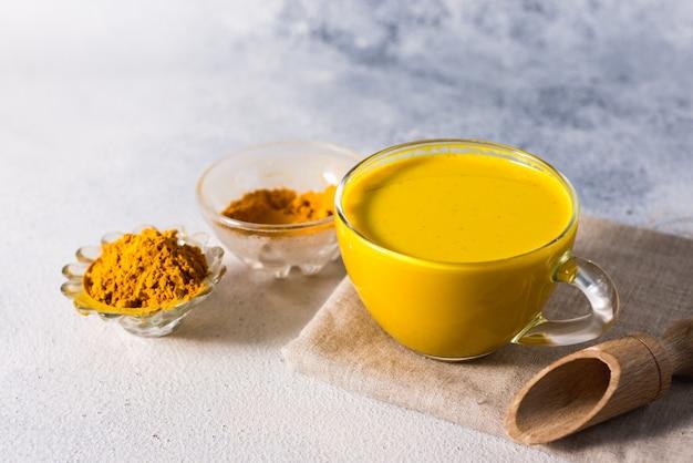Goldene gelbwurzmilch auf der weißen oberfläche mit gewürzzimt und -bestandteilen