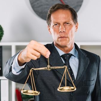 Goldene gerechtigkeitsskala hinter dem rechtsanwalt, der das dokument auf schreibtisch unterzeichnet