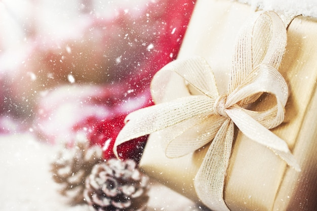 Goldene geschenk mit einem weißen bogen und tannenzapfen