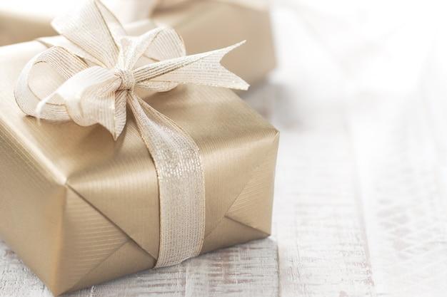 Goldene geschenk mit einem weißen bogen