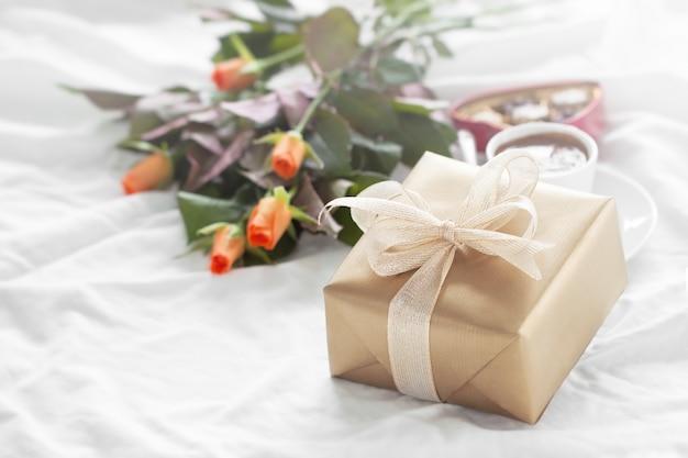 Goldene geschenk-paket mit einem strauß blumen und pralinen