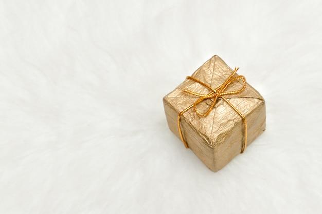 Goldene geschenkbox auf einem weißen hintergrund, kopienraum