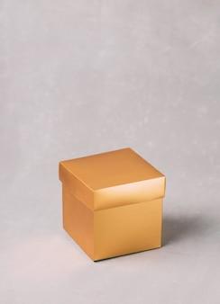 Goldene geschenkbox auf grauem hintergrund. platz kopieren. festliche urlaubskulisse.