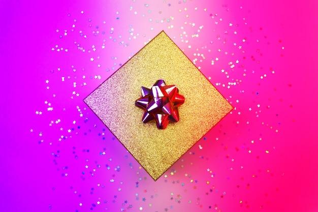 Goldene geschenkbox mit band und konfetti