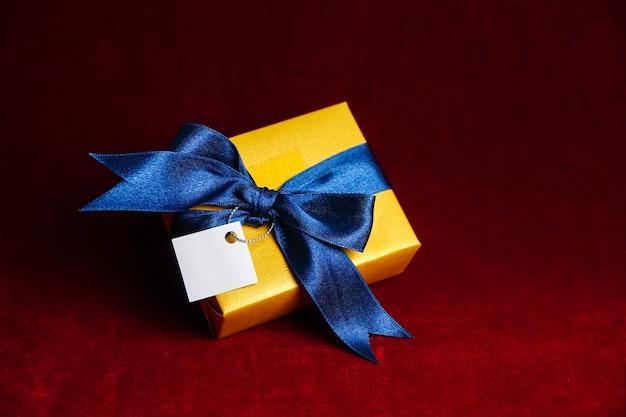 Goldene geschenkbox mit blauer schleife auf rotem grund