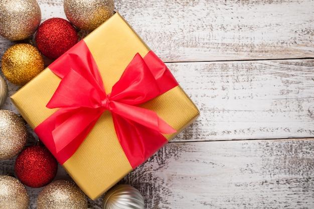 Goldene geschenkbox mit einem roten band gebunden.