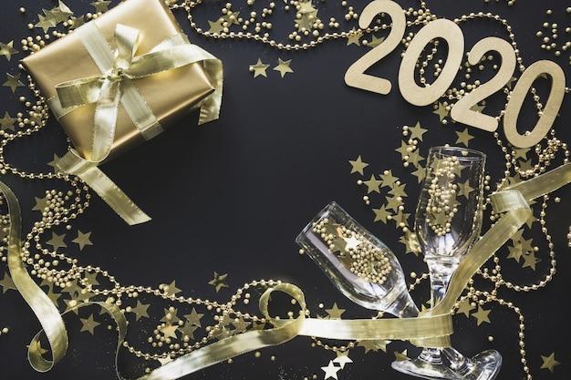 Goldene geschenkbox mit glaschampagner auf schwarzem