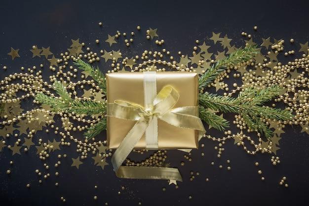 Goldene geschenkbox mit goldband auf draufsicht der schwarzen hintergrund weihnachtsgeschenk ebenenlage. festliches banner. weihnachtsmuster.