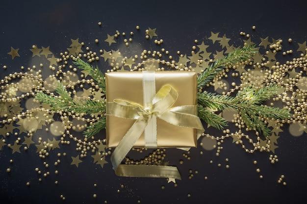 Goldene geschenkbox mit goldband auf schwarzem