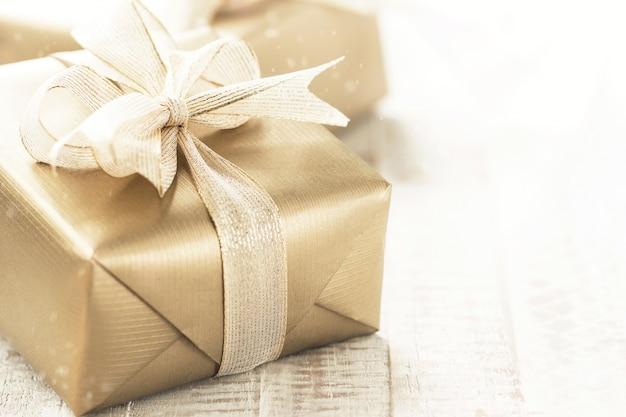 Goldene geschenkboxen mit schönem band und bogen auf einem hellen glänzenden hintergrund, feiertagskonzept, horizontal mit kopienraum