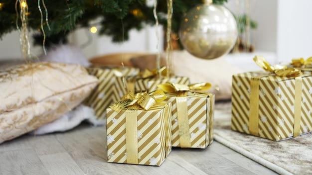 Goldene geschenkkisten unter dem weihnachtsbaum
