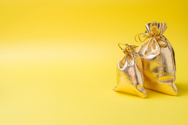 Goldene geschenktüte auf gelb