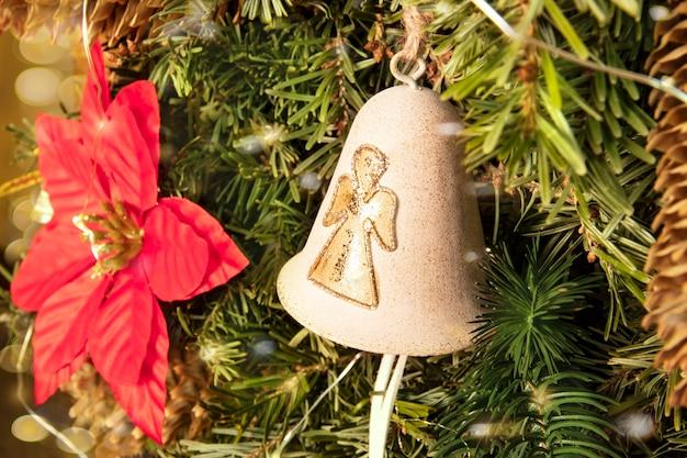 Goldene glocke mit einem weihnachtsengel auf einem traditionell geschmückten baum mit einem weihnachtsstern