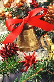 Goldene glocke mit roter farbbandbogen- und -weihnachtsdekoration